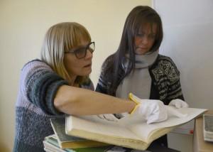 Daglig leder ved DigForsk Tana Torill Dagfinnsdatter og spesialrådgiver ved Finnmark fylkesbibliotek Helena Maliniemi studerer de originale protokollene.   Blant disse er blant annet innskrivningsjournal til Vadsø fødehjem.  Foto: Sonja Siltala.
